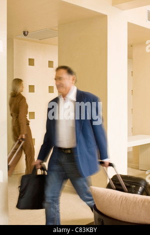 Businessman rolling luggage in walkway - Stock Photo