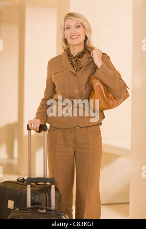 Smiling businesswoman rolling luggage - Stock Photo