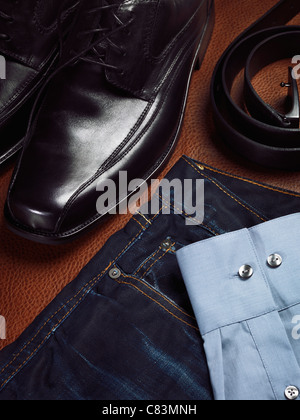 Mens fashion still life. Artistic closeup of dress shoes, jeans, a belt and a shirt. - Stock Photo