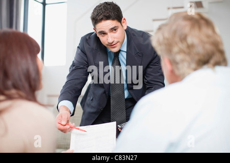 Businessman working with couple - Stock Photo