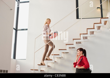Businesswoman climbing stairs in office - Stock Photo