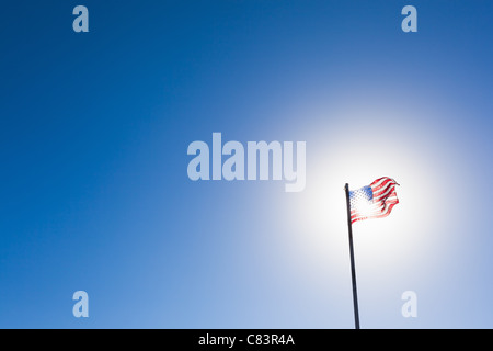 American flag against sun and blue sky - Stock Photo