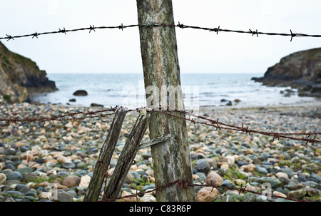 Barbed wire fence on rocky beach - Stock Photo