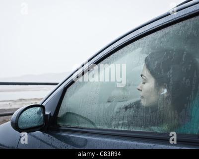 Teenage girl sitting in car by beach - Stock Photo