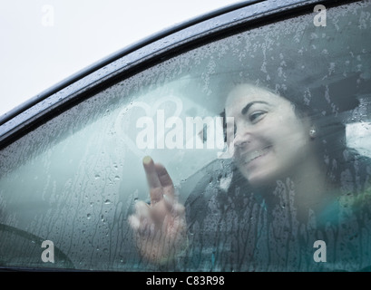 Teenage girl drawing on wet car window - Stock Photo