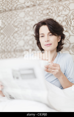 Woman reading newspaper in bed - Stock Photo
