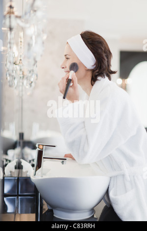 Woman in bathrobe applying makeup - Stock Photo