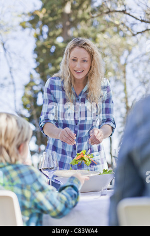 Mother serving children salad outdoors - Stock Photo