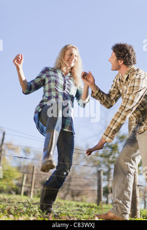 Couple climbing over wire fence outdoors - Stock Photo
