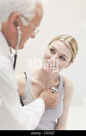 Doctor listening to patient's heartbeat - Stock Photo