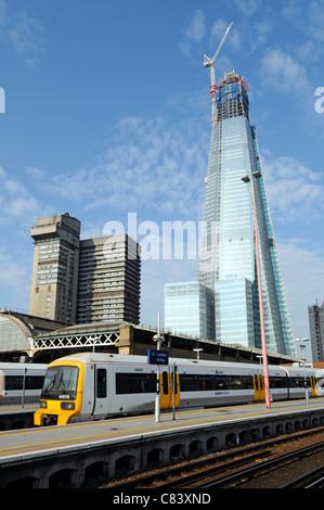 Work in progress at Shard landmark skyscraper building site under construction beyond London Bridge train station - Stock Photo