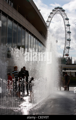 Playing in the Appearing Rooms fountains outside the Festival Hall on London's South Bank - Stock Photo
