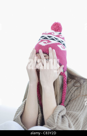 Teenage girl covering face with hands - Stock Photo