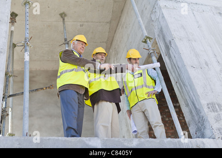 Businessman and workers talking on site - Stock Photo