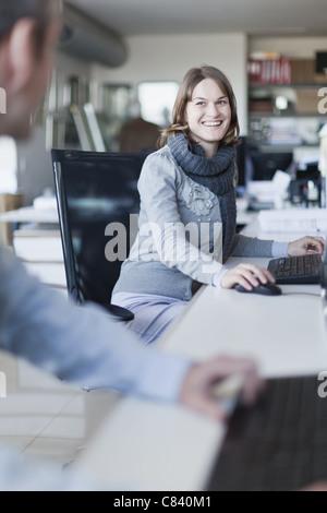 Smiling businesswoman talking at desk - Stock Photo