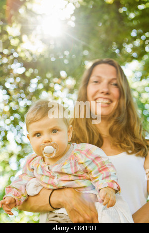 Mother holding baby with pacifier - Stock Photo