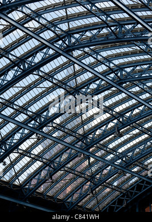 Clock tower of St Pancras station visible through the ornate glass roof of the entrance hall of the building - Stock Photo