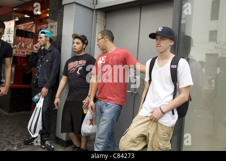 Young men, all smoking, hang out on 34th Street in Manhattan. - Stock Photo