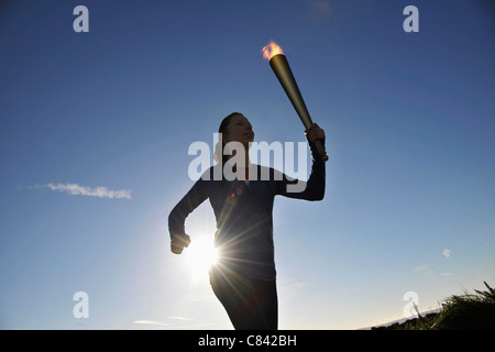 Athlete running with flaming baton - Stock Photo