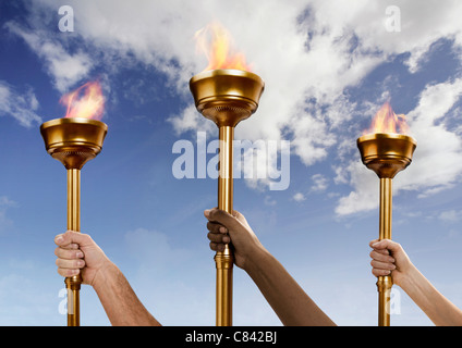 Hands holding flaming batons - Stock Photo