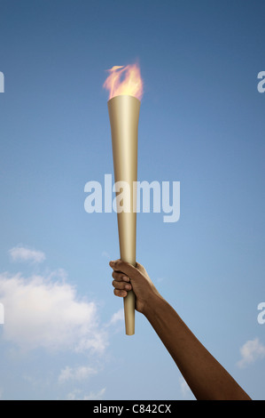Hand holding flaming baton - Stock Photo