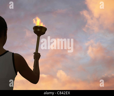 Athlete holding flaming baton - Stock Photo