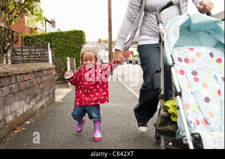 Toddler girl walking with mother - Stock Photo