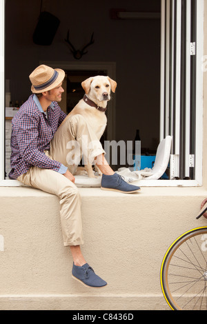 Man sitting with dog in windowsill - Stock Photo