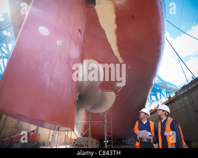 Workers standing on shipbuilding site - Stock Photo