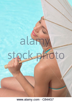 Woman sitting by pool under umbrella - Stock Photo