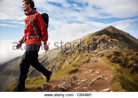 Hiker walking on rocky mountaintop - Stock Photo