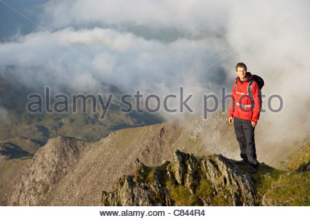 Hiker overlooking view from mountaintop - Stock Photo