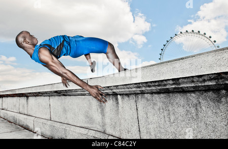 Athlete vaulting over stone wall - Stock Photo
