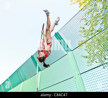 Athlete vaulting over wire fence - Stock Photo