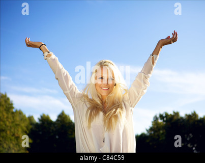 Cute young female outside on a sunny day, raising her arms above her head. - Stock Photo