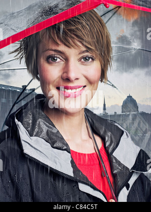 Smiling woman under umbrella in rain