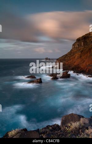 Waves crashing on rocky cliffs - Stock Photo