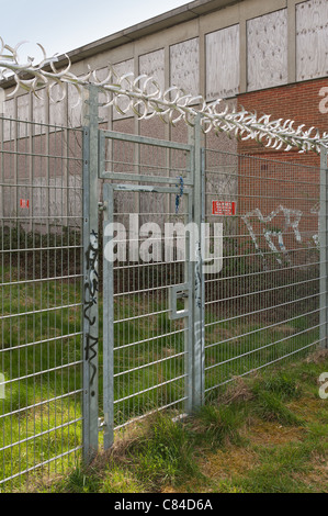 Keep out security fence protecting from burglary against an early morning sky - Stock Photo