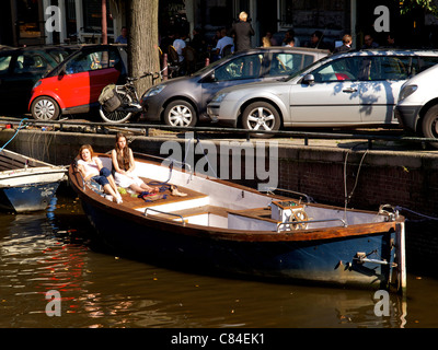 Two pretty girls speding their lunch break in the sun on a boat in a canal in Amsterdam, the Netherlands - Stock Photo