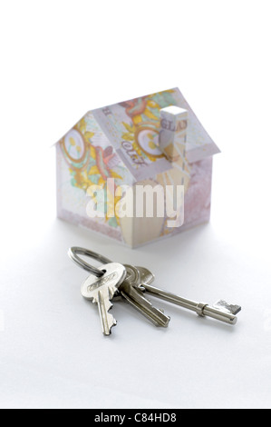 Bunch of keys and model house folded with British pound banknotes - Stock Photo