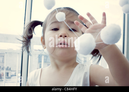 Little girl playing with hanging decoration - Stock Photo