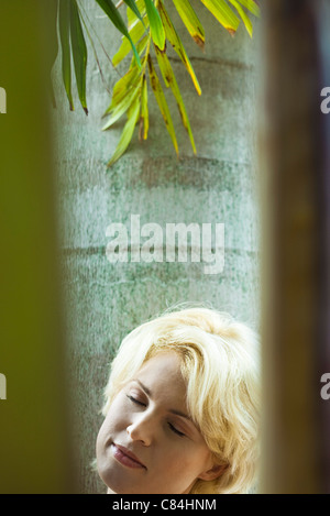 Woman relaxing under palm tree - Stock Photo