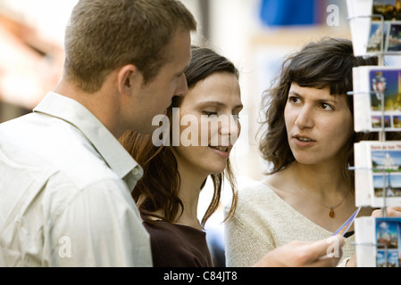 Tourists looking at postcards - Stock Photo