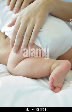 Mother's hand touching baby's leg - Stock Photo