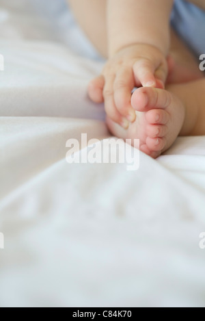Baby touching its foot, cropped - Stock Photo