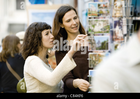 Female tourists looking at postcards - Stock Photo