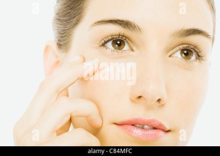 Woman applying undereye cream, close-up - Stock Photo