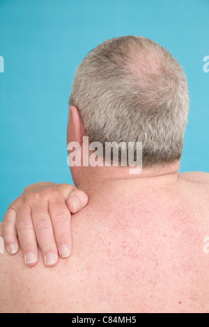 Man with hand over left shoulder - Stock Photo