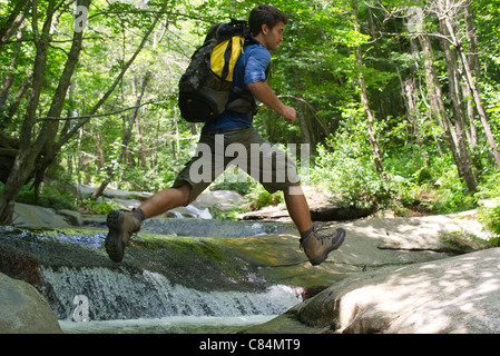 Man jumping over stream through woods - Stock Photo