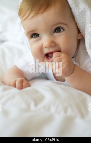 Baby lying on blanket, sticking thumb in mouth, portrait - Stock Photo
